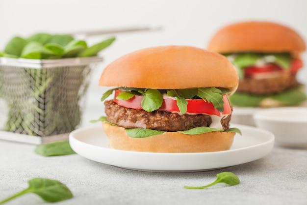 Zdrowe wegetariańskie burgery bez mięsa na okrągłym talerzu ceramicznym z warzywami i szpinakiem na jasnym tle.