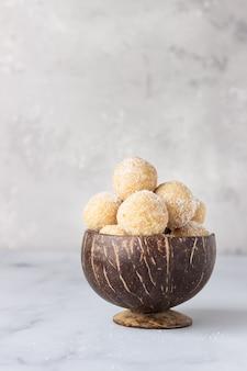 Zdrowe wegetariańskie kulki z ciecierzycy, masła orzechowego i kokosa w drewnianej misce