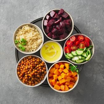 Zdrowe wegetariańskie składniki do gotowania marokańskiej sałatki. ciecierzyca, pieczona dynia i buraki, komosa ryżowa i warzywa widok z góry