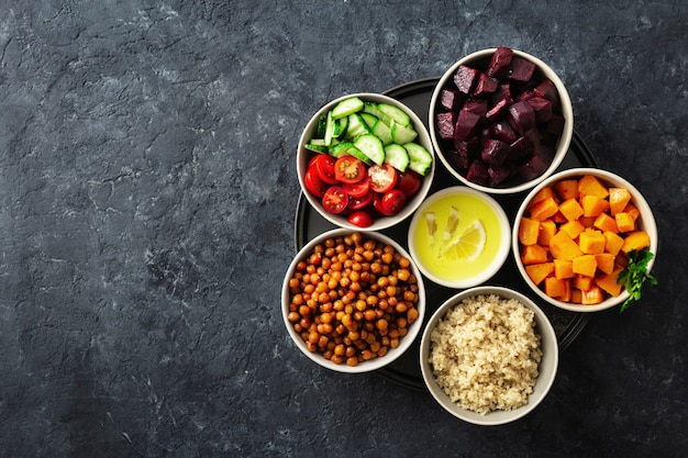 Zdrowe wegetariańskie składniki do gotowania marokańskiej sałatki. ciecierzyca, pieczona dynia i buraki, komosa ryżowa i warzywa.