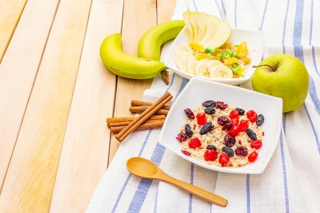 Zdrowe wegetariańskie (wegańskie) śniadanie z płatkami owsianymi i owocami. drewniany stół