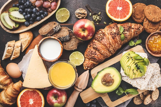 Zdrowe zbilansowane śniadanie na ciemnym tle. musli, mleko, sok, rogaliki, ser, herbatniki.