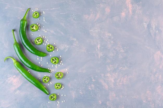 Zdrowe zielone papryczki chili i plastry na kamiennej powierzchni