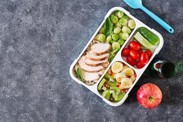 Zdrowe zielone pojemniki przygotowujące posiłek z filetem z kurczaka, ryżem, brukselką, warzywami i owocami napowietrznymi z kopią. kolacja w pudełku na lunch. widok z góry. leżał płasko