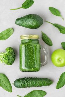 Zdrowe zielone smoothie w słoiku na wynos ze szpinaku, brokułów, awokado, jabłka i ogórka. widok z góry. leżał płasko. koncepcja surowego wegańskiego jedzenia. orientacja pionowa