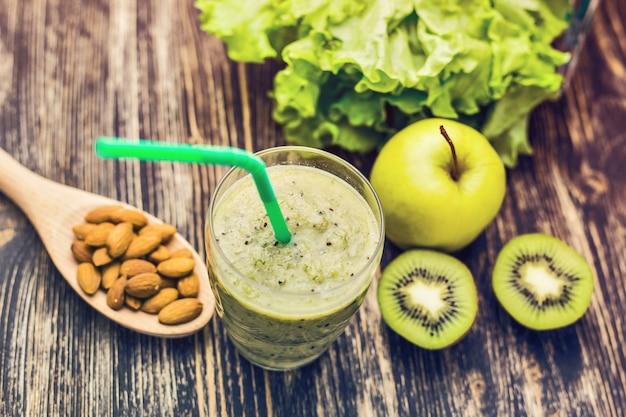 Zdrowe zielone smoothie z kiwi, jabłkiem na rustykalnym drewnie