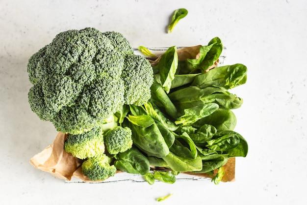 Zdrowe zielone warzywa z brokułami i szpinakiem w drewnianej tacy.