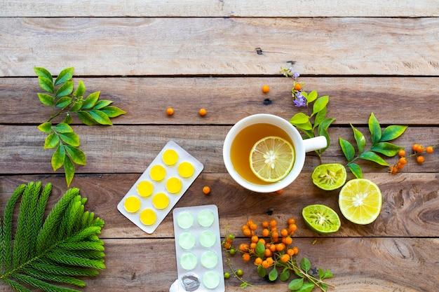 Zdrowe ziołowe napoje gorący miód, herbata cytrynowa i pastylka do ssania