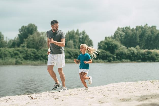 Zdrowe życie. pełna długość wesołego ojca i córki w sportowych ubraniach biegających razem nad brzegiem rzeki