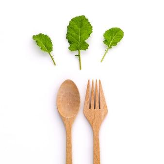 Zdrowego karmowego pojęcia świeża organicznie zieleń opuszcza z drewnianym rozwidleniem i łyżką.