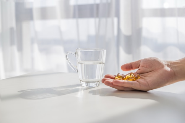 Zdrowego stylu życia, medycyna, suplementy odżywcze i pojęcia ludzi - zamknąć płci męskiej ręce trzyma pigułki z kapsułek oleju z wątroby dorsza i szkła wodnego