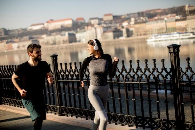 Zdrowi biegacze biega w miasto pejzażu miejskiego tle