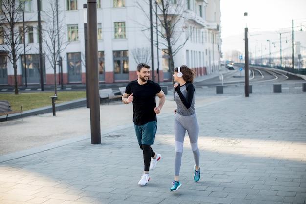 Zdrowi biegacze biega w mieście z pejzażem miejskim w tle