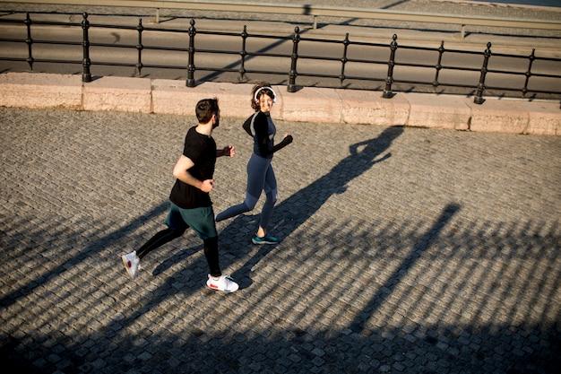 Zdrowi biegacze biega w mieście z pejzażu miejskiego tłem