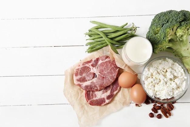 Zdrowi karmowi składniki na białym drewnianym stole
