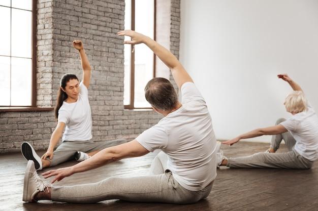 Zdrowi ludzie w wygodnych ubraniach siedzą na podłodze podczas jogi