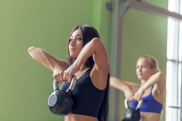 Zdrowi młodzi sportowcy robią ćwiczenia z kettlebells, w studio fitness