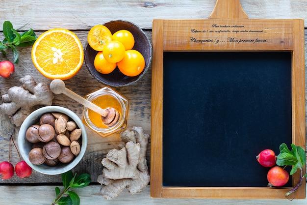 Zdrowi produkty dla odporności zwiększającej na drewnianym tle z kopii przestrzeni odgórnym widokiem. cytryna, orzechy, imbir na układ odpornościowy