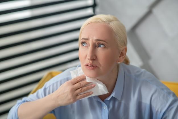 Zdrowie, dolegliwości. nieszczęśliwa dorosła kobieta w lekkiej bluzce z papierową serwetką przy szyi, patrząc smutno w górę i na bok.