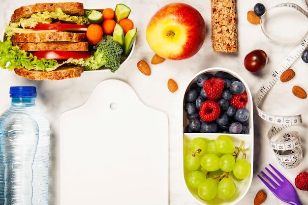 Zdrowie i fitness jedzenie w pojemnikach na lunch, taśma miernicza i alarm