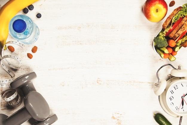 Zdrowie i fitness jedzenie w pudełku na lunch, taśma miernicza, hantle a