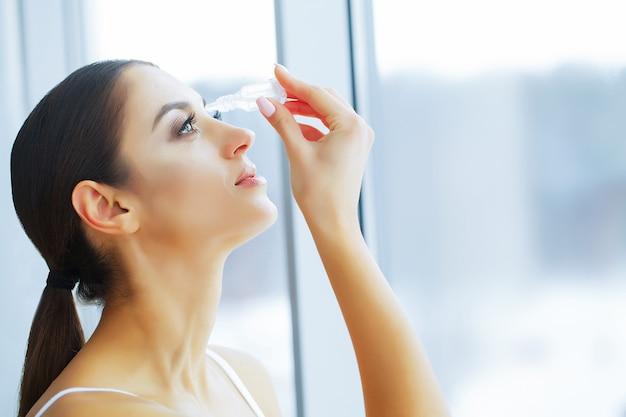 Zdrowie i piękno. opieka oka. piękna młoda kobieta gospodarstwa krople
