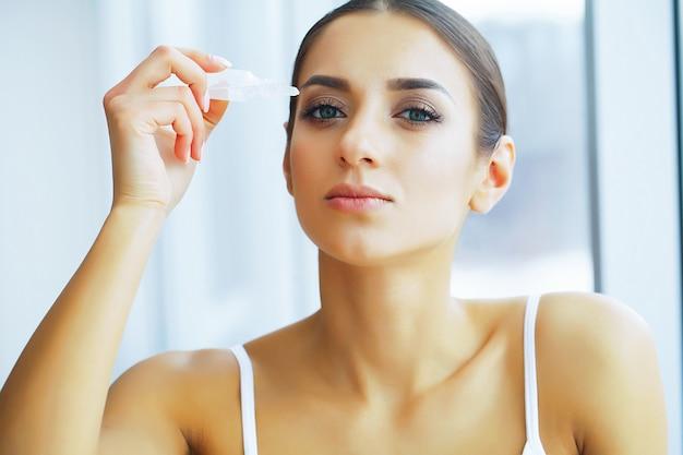 Zdrowie i piękno. piękna młoda dziewczyna z kroplami do oczu. kobieta trzyma krople do oczu w dłoni. zdrowy wygląd.