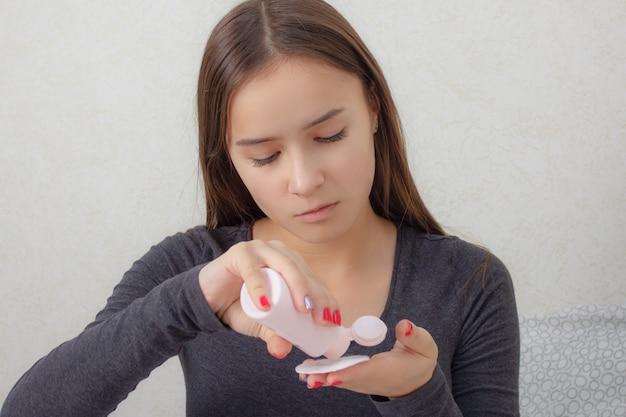 Zdrowie i piękno. pielęgnacja twarzy młoda dziewczyna ociera twarz tonikiem, odżywczym balsamem.