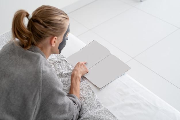 Zdrowie kobiet. spa i wellness. kobieta z maską relaks leżąc na łóżku czytając czasopismo. projekt makiety