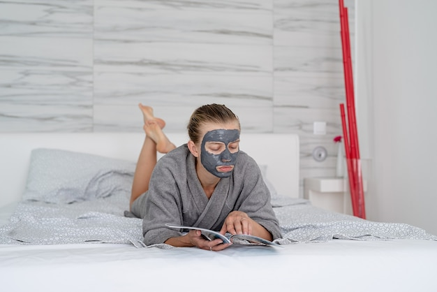 Zdrowie kobiet. spa i wellness. kobieta z maską relaksacyjną leżącą na łóżku czytającą czasopismo