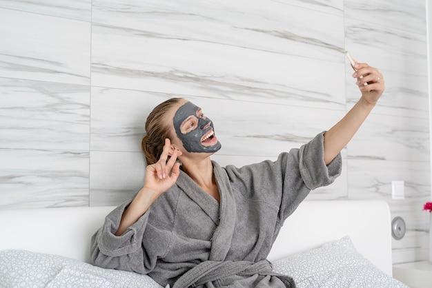 Zdrowie kobiet. spa i wellness. kobieta z maską relaksacyjną siedzącą na łóżku za pomocą urządzenia mobilnego