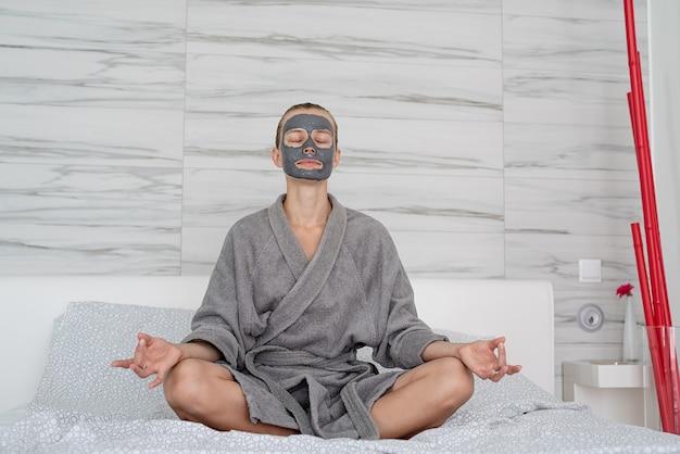 Zdrowie kobiet. spa i wellness. kobieta z maską relaksacyjną siedzącą na łóżku