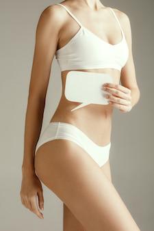 Zdrowie kobiety. modelka trzyma pustą kartę w pobliżu żołądka. młoda dziewczyna dla dorosłych z papieru na znak lub symbol na białym tle na szarym tle studio. wytnij część ciała. problem medyczny i rozwiązanie.
