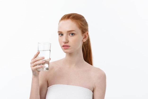 Zdrowie, ludzie, jedzenie, sport, styl życia i piękno - uśmiechnięta młoda kobieta ze szklanką wody.