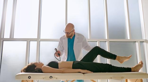 Zdrowie pleców dziewczyna wykonuje ćwiczenia na plecy, które przywracają funkcje fizyczne w nowoczesnej rehabilitacji...