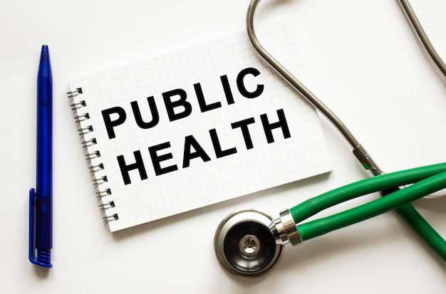 Zdrowie publiczne jest zapisane w zeszycie na białym stole obok pióra i stetoskopu. pojęcie medyczne