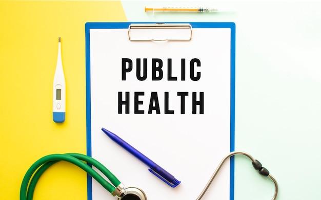 Zdrowie publiczne tekst na papierze firmowym w folderze medycznym na pięknym tle. stetoskop, termometr i długopis.