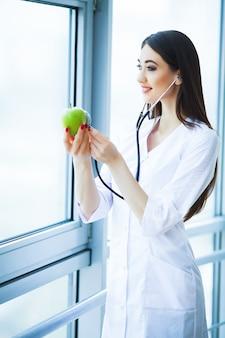 Zdrowie. zdrowa dieta. doktorski dietetyczka trzyma w rękach świeżego zielonego jabłka i ono uśmiecha się. piękny i młody lekarz.