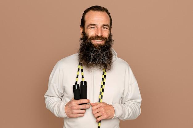 Zdrowy brodaty mężczyzna ze skakanką na szyi