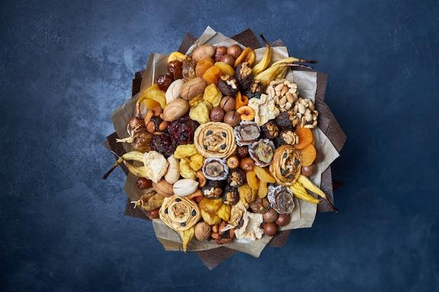 Zdrowy bukiet suszonych owoców i orzechów, widok z góry na ciemnoniebieski