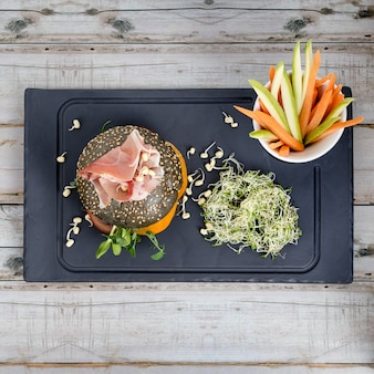 Zdrowy burger z hamonem, pomidorami, mikro zieleniną i czarnymi pełnoziarnistymi bułkami, paluszkami warzywnymi na czarnej desce z łupków nad drewnianym stołem. czyste jedzenie, dieta, detox koncepcja żywności.