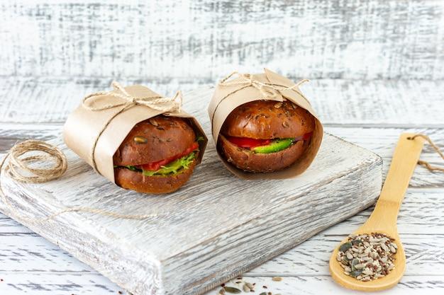 Zdrowy burger z łososia z awokado i pomidorem podawany w papierze rzemieślniczym na drewnianym tle.