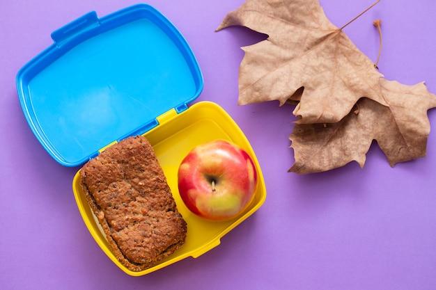 Zdrowy chleb w pudełku z jabłkiem w jasnych kolorach