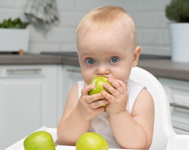 Zdrowy chłopczyk z dużymi niebieskimi oczami siedzi na dziecięcym krzesełku w kuchni zjada zielone jabłka.
