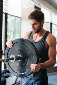 Zdrowy człowiek fitness ze sztangą. rozważny