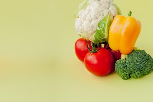Zdrowy, czysty układ jedzenia, wegetariańskie jedzenie i dieta koncepcja żywienia. różnorodni świeżych warzyw składniki dla sałatki na kolor żółty zgłaszają tło, odgórny widok, rama, sztandar.