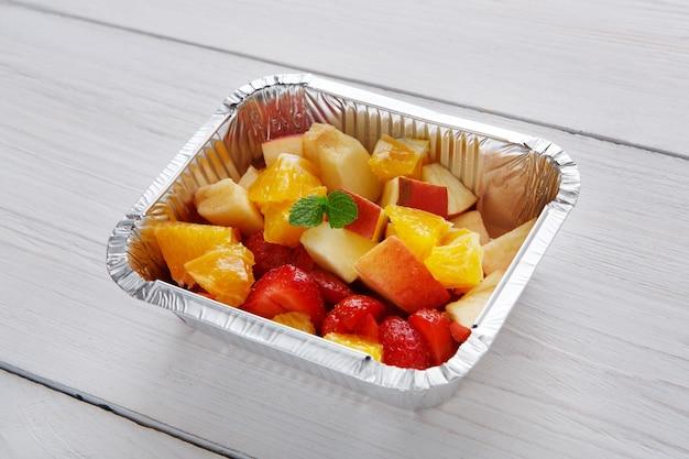 Zdrowy deser. sałatka ze słodkich owoców zbliżenie w pudełku dostawy folii.