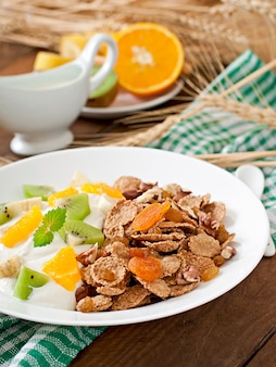 Zdrowy deser z musli i owocami w białym talerzu na stole