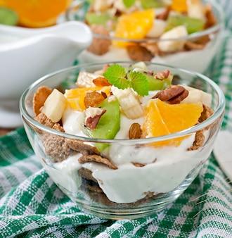 Zdrowy deser z musli i owocami w szklanej misce na stole