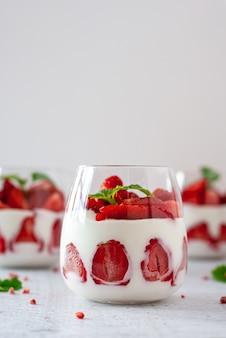 Zdrowy deser z truskawkami, jogurtem i twarożkiem w przezroczystym szkle.